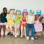 Vidám gyerekek ülnek egymás mellett egy padon